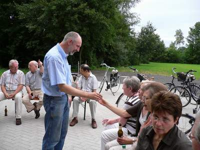 Der Vorsitzende aus Büren schenkt den Damen einen 'Roten' ein.
