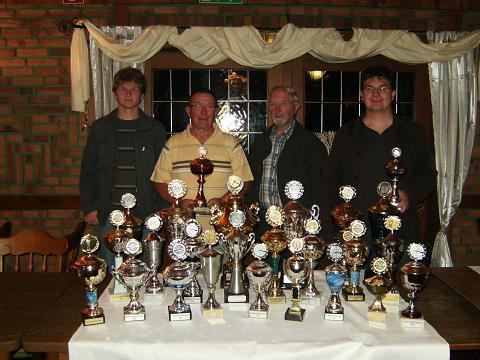 Die Ludgerus-Schützen aus Harwick mit dem Familientrio Vater Paul Finnah und Söhnen Thomas und Ulrich sowie Hartmut Lieneweg und ein paar der gewonnenen Pokalen seit Ihrem bestehen.